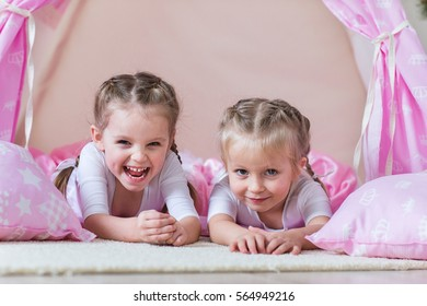 Two little girls play in a teepee
