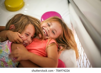 Two little girls in playground. Caucasian girls lying on floor and hugging.