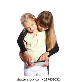 Two little girls playing with a digital tablet