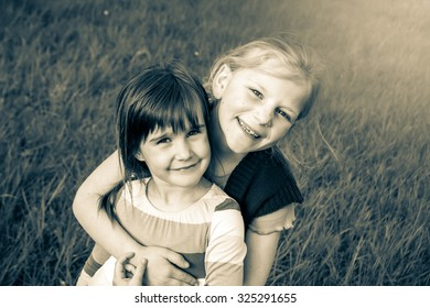 Two little girls playing in the grass