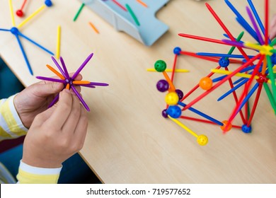 Two little girls playing with lots of colorful plastic sticks kit indoors. kids having fun with building  geometric figures and learning mathematics in preschool or primary class of school
