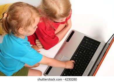 Two little girls playing on laptop on a light background