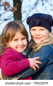 Two little girls playing outside in autumn