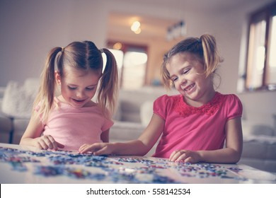 Two little girls playing with a puzzle.