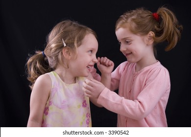 Two little girls playing together on a black background.