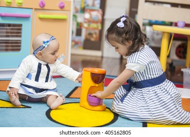 Two little girls playing with toy kitchen