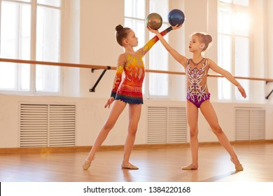 Two little girls practicing rhythmic gymnastics in class, copy space