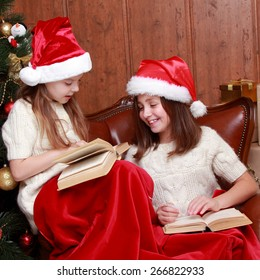 Two little girls reading in a book near the christmas tree on Holiday theme/Charming kids reading books on Christmas time