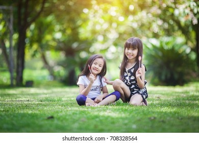 Two little girls relaxing play in the park and eat lollipops.