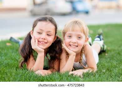 Two little girls in roller skates laying on the grass and having fun