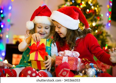 Two little girls in the Santa hat open Christmas present under the Christmas tree