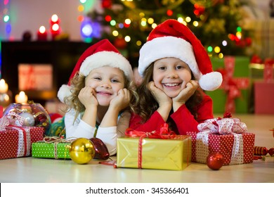 Two little girls in the Santa hat with the Christmas gift under the tree