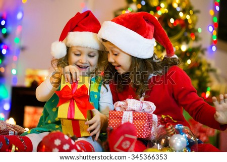 5d05835de1351 Two little girls in the Santa hat open Christmas present under the Christmas  tree
