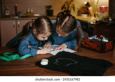 Two little girls sew a mask at home. They draw a pattern on paper. Nearby is fabric and multi-colored threads. Seamstress