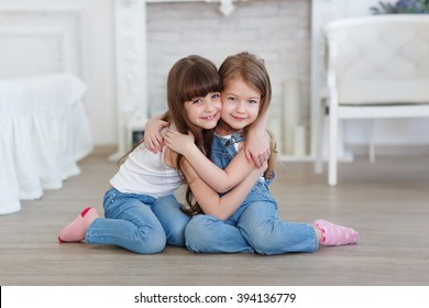 two little girls sisters hugging