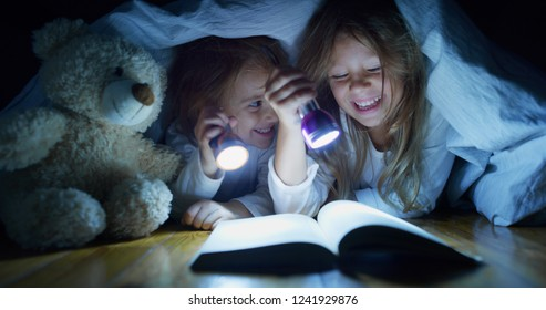 Two little girls sisters (kids) read stories and having fun, laughing in the dark under the blanket illuminating with a torch. Concept: Love, Family, Dreams