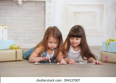 two little girls sisters playing on tablet computer