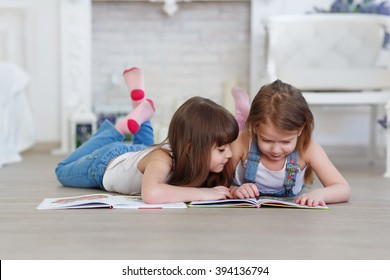 two little girls sisters reading a book lying on the floor