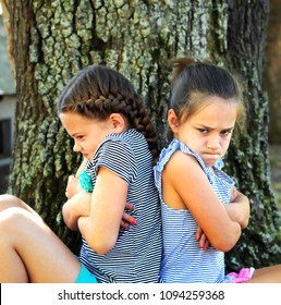 Two little girls sit back-to-back, outside besides a tree.  They both have their arms crossed and their expressions are angry.