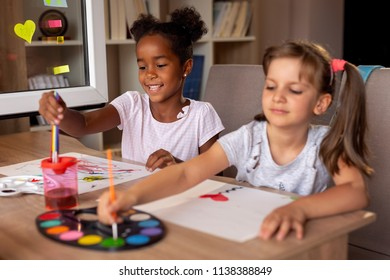 Two little girls sitting at a desk, painting with water colors and having fun. Focus on the girl on the left