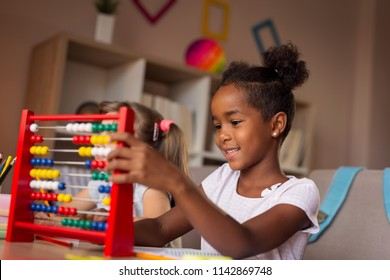 Two little girls sitting at a desk, doing their homework; little girl practising math using abacus while doing homework