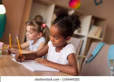 Two little girls sitting at a desk, writing in their notebooks, doing a math homework and studying for school.