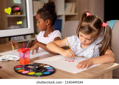 Two little girls sitting at a desk, painting with water colors and having fun