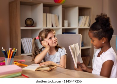 Two little girls sitting at a desk at home, studying for school and examining each other; first graders doing their homework and reading books