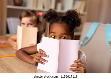 Two little girls sitting at a desk at home, hiding behind books and peeking; first graders doing their homework and reading books