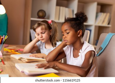 Two little girls sitting at a desk at home, reading books and studying for an exam, tired and unhappy