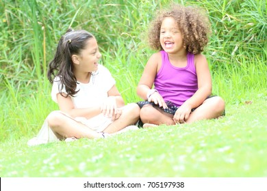 Two little girls are sitting in the grass laughing and talking to each other. One girl is hispanic and the other is African American.