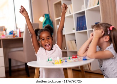 Two little girls sitting in a playroom, playing a ludo board game; one of them just won the game, while the other one is sad. Focus on the girl on the left
