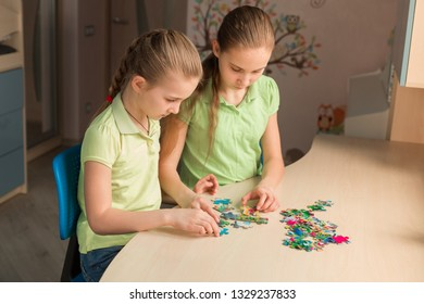 Two little girls solving puzzle together sitting at the table