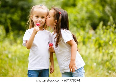 Two little girls stand and eat a lolipop in the park, outdoor summer portrait. sister kisses a sister