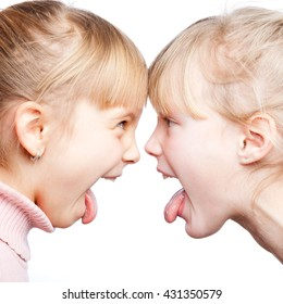 Two little girls stick out tongues teasing each other face to face