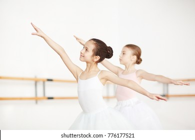 Two little girls stretching their arms during ballet exercise in classroom