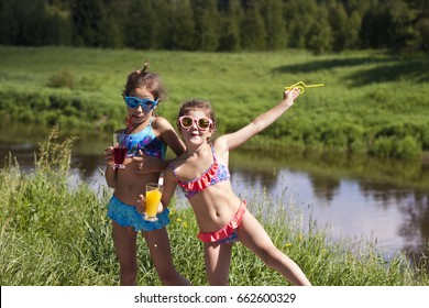 2508ae435604 Two little girls in sunglasses are having fun and drinking juice at a  children's party outdoors