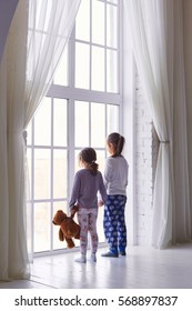 two little girls in their pajamas and are looking at a large window