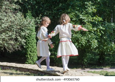 two little girls in traditional Ukrainian dress jumping in the park