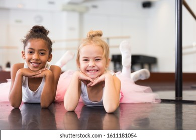 Two little girls in tutu rehearsing in classical dance school