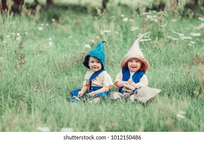 Two little gnomes have a nice time in a green forest. Childhood, happiness, summer concept