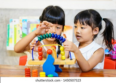 Two little happy asian girl intend to playing colorful wooden toys in kindergarten classroom.