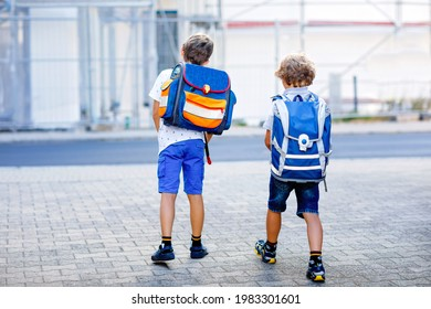 Two little kid boys with backpack or satchel. Schoolkids on the way to school. Healthy adorable children, brothers and best friends outdoors on the street leaving home. Back to school. Happy siblings.