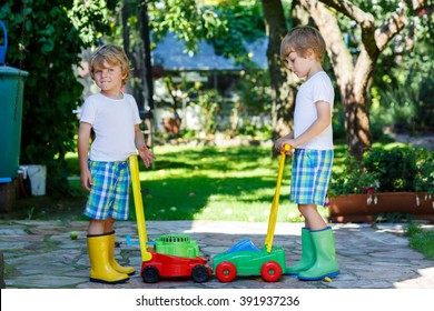 Two little kid boys, brothers playing with lawn mower machines toys in summer garden on sunny day. Siblings having fun. Family, garden, gardening, lifestyle