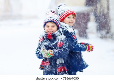 Two little kid boys in colorful clothes, outdoors during snowfall. Active leisure with children in winter on cold snowy days. Happy siblings having fun with snow. Best friends playing together