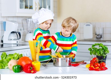 Two little kid boys cooking pasta spaghetti with fresh vegetables and tomato sauce in domestic kitchen. Siblings children in colorful shirts having fun with helping at home.