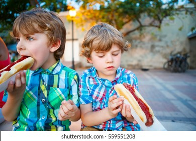 Two little kid boys eating hot dogs outdoors. Siblings enjoying their meal. Hotdog as unhealthy food for children.