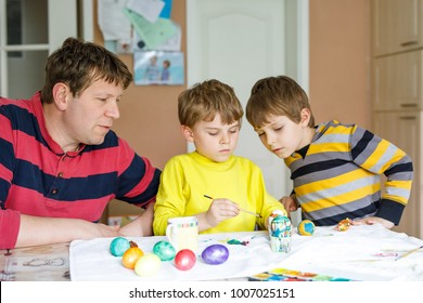 Two little kid boys and father coloring eggs for Easter holiday in domestic kitchen, indoors. Children and dad having fun together with painting colors and celebrating feast.