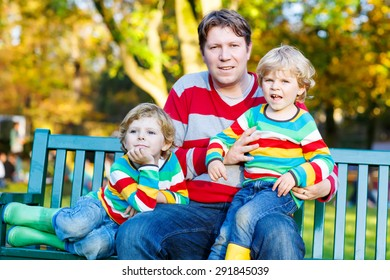 Two little kid boys and young father sitting together in colorful clothing. Happy siblings and their dad having fun in autumn park on warm day.