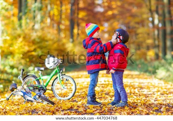 Deux petits garçons, meilleurs amis dans le parc d'automne. Un frère aîné aide un jeune enfant à mettre son casque de vélo. Des frères et soeurs actifs avec des vélos.Bonne famille